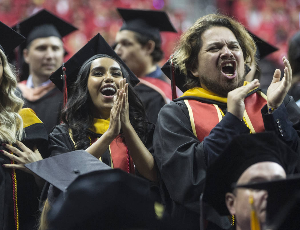 Priscilla Arguello, left, and Angel Alonso cheer for classmates after earning their degree in Couple and Family Therapy during UNLV's winter graduation ceremony on Tuesday, Dec. 18, 2018, at the T ...