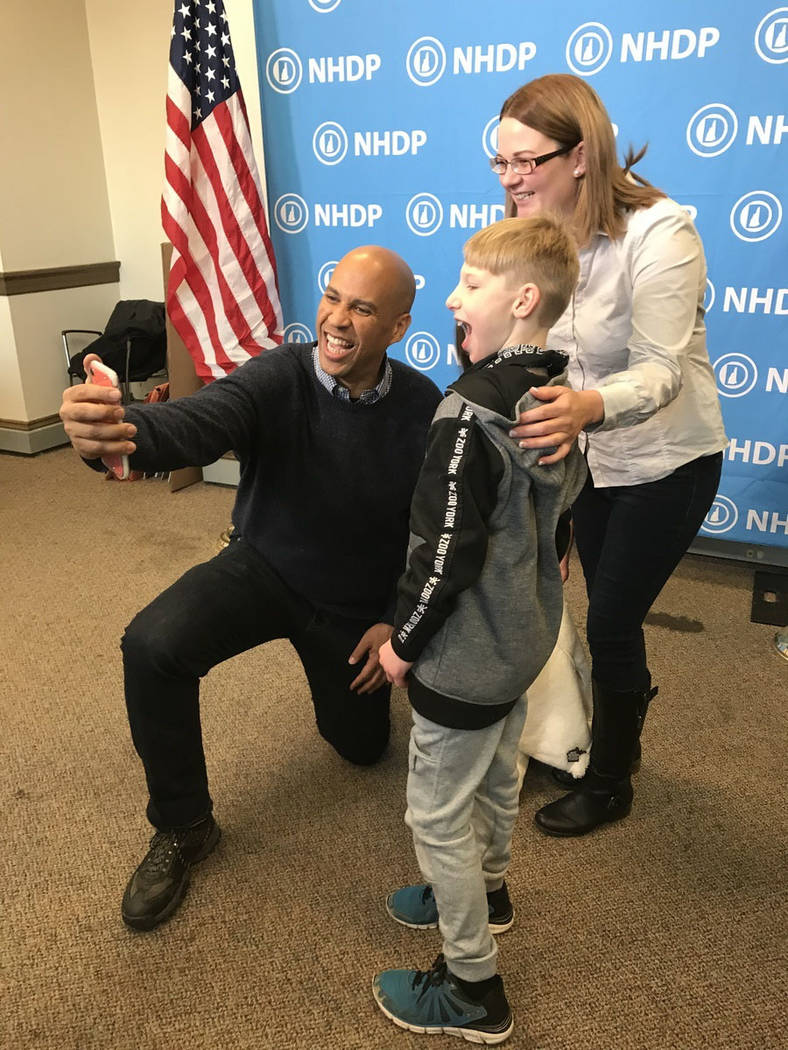 Sen. Cory Booker, D-N.J. took time to shoot selfies with New Hampshire Democrats, Saturday, Dec. 8, 2018, during a celebration he headlined. Booker was the only Democrat from out of state and cons ...