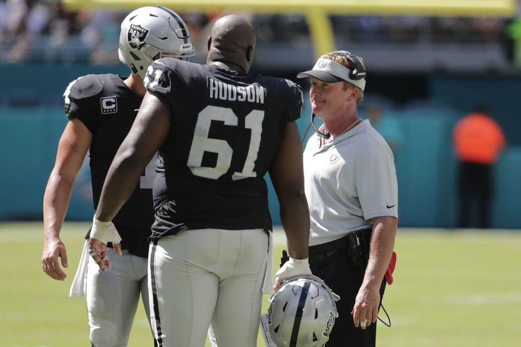 Oakland Raiders head coach Jon Gruden talks with center Rodney Hudson (61) and quarterback Derek Carr, left rear, during the second half of an NFL football game against the Miami Dolphins, Sunday, ...