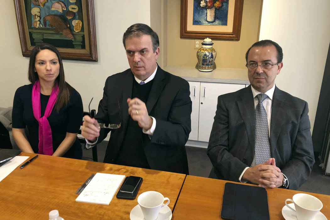 Mexican Foreign Minister Marcelo Ebrard, center, talks to reporters, Monday Dec. 3, 2018 at the Mexican Embassy in Washington. Ebrard is flanked by Paulina Chavez Alonso, head of the embassy's Pr ...