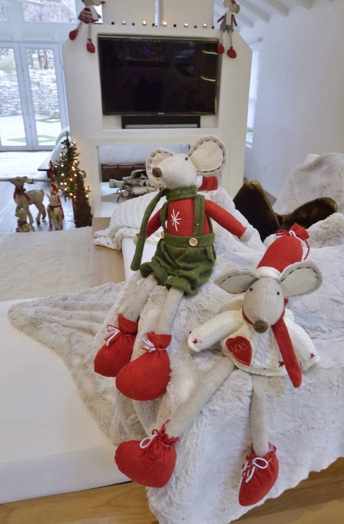 """Fun Christmas decorations rest on the L-shaped chaise lounge covered in """"high-maintenance white chenille."""" (Bill Hughes/Real Estate Millions)"""