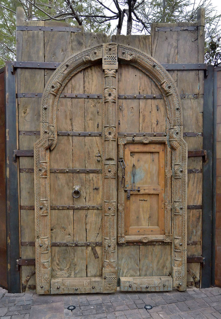 A pair of 4-inch-thick teak monastery doors, over 600 years old, divide the side and backyards. (Bill Hughes/Real Estate Millions)
