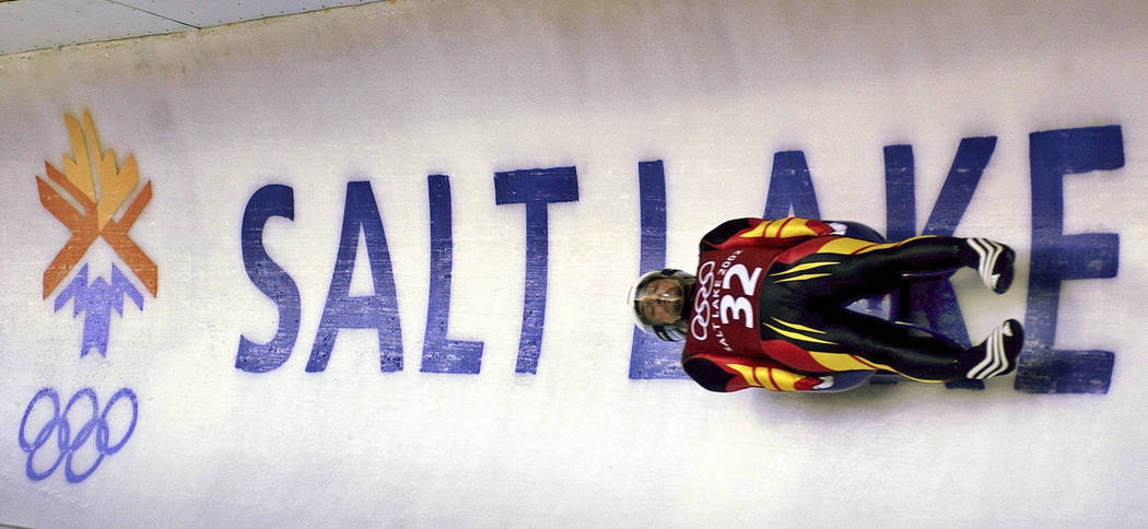 Georg Hackl, of Germany, speeds past an Olympic logo during a Feb. 9, 2002, practice run for the men's singles luge at the 2002 Salt Lake City Winter Olympics in Park City, Utah. (AP Photo/Elise A ...