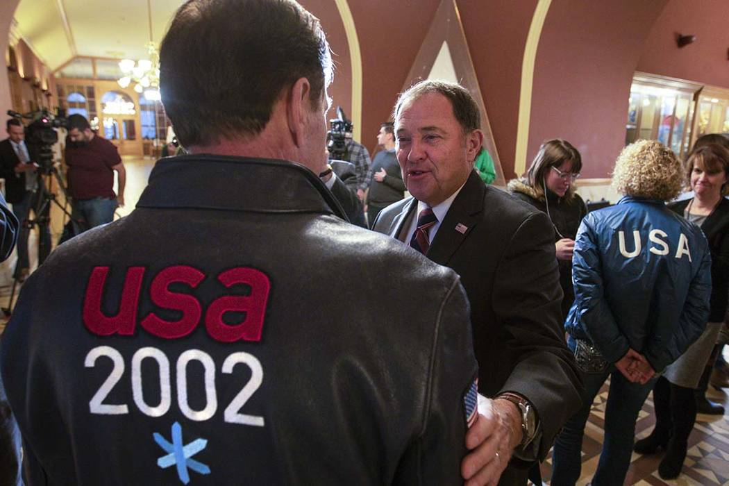 Gov. Gary Herbert, center, talks with Fraser Bullock, chief operating officer of the 2002 Winter Games, after the USOC choose Salt Lake over Denver to bid on behalf of the US for future Winter Gam ...
