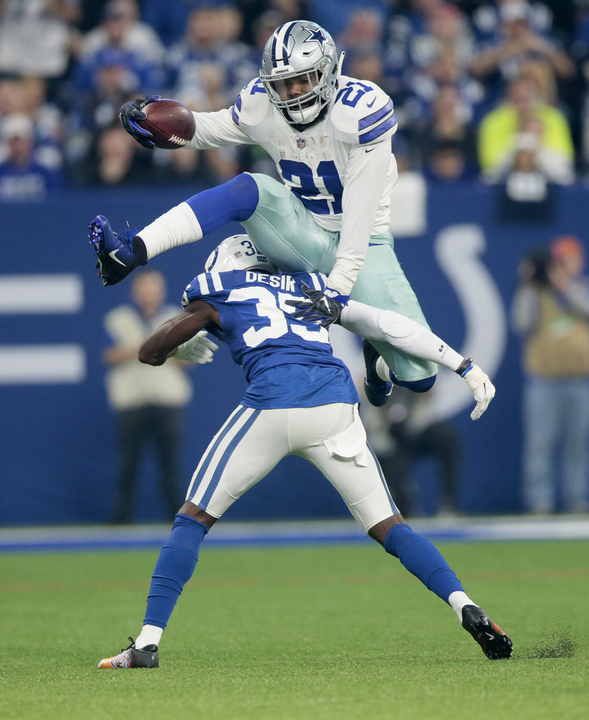 Dallas Cowboys running back Ezekiel Elliott leaps over Indianapolis Colts cornerback Pierre Desir during the first half of an NFL football game, Sunday, Dec. 16, 2018, in Indianapolis. Indianapoli ...