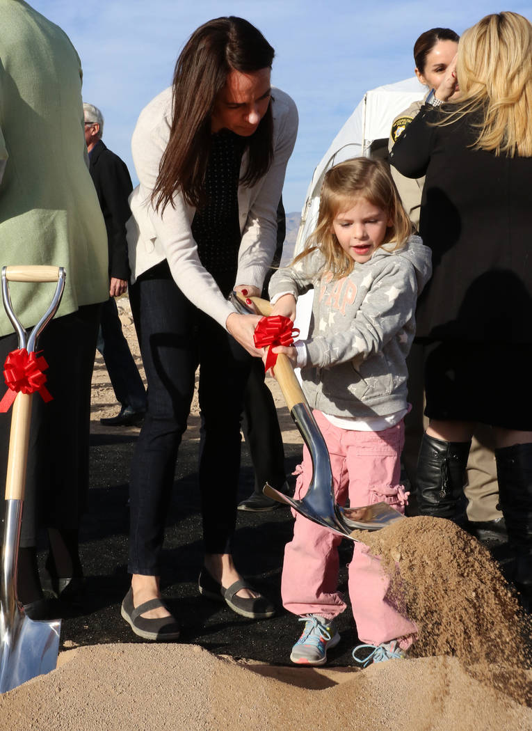 Nicole Beck, wife of Las Vegas Metropolitan Police Officer Alyn Beck, who was killed in the line of duty Sunday, June 8, 2014, turns the soil with her daughter Katriann, 5, after participating in ...