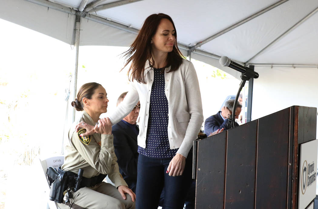 Nicole Beck, wife of Las Vegas Metropolitan Police Officer Alyn Beck, who was killed in the line of duty Sunday, June 8, 2014, comforted by Capt. Sasha Lankin, left, as she takes the podium during ...