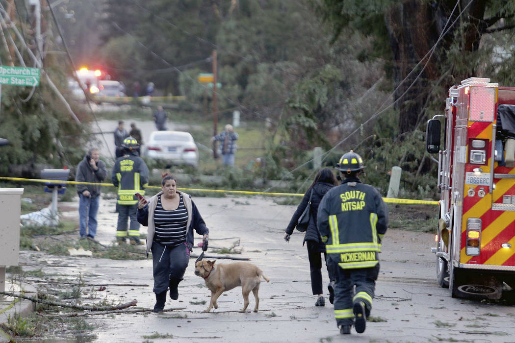 Residents and emergency personnel on Harris Road in Port Orchard, Wash., on Tuesday, Dec. 18, 2018, after a tornado touched down. A rare tornado touched down in a Seattle suburb on Tuesday, damagi ...