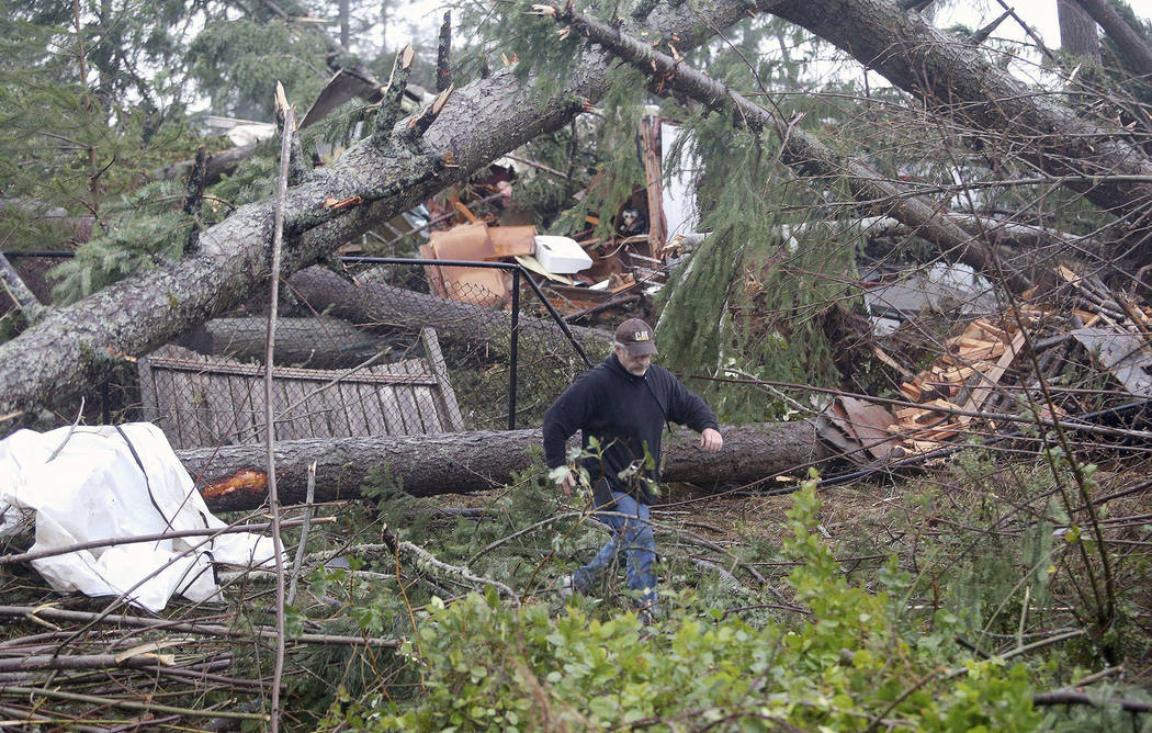 Matt Hargis walks through downed trees behind the Walmart in Port Orchard, Wash., on Tuesday, Dec. 18, 2018, after a tornado touched down. Based on radar imagery and video evidence, a tornado touc ...