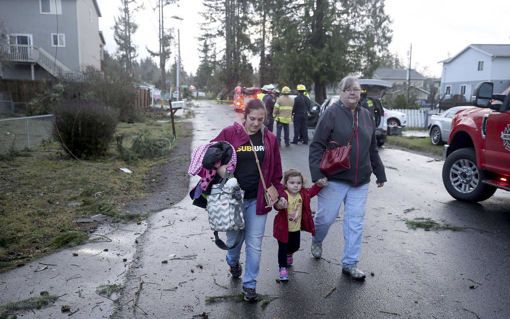 Residents evacuate from their Harris Road in Port Orchard, Wash., on Tuesday, Dec. 18, 2018, after a tornado touched down. A rare tornado touched down in a Seattle suburb on Tuesday, damaging seve ...
