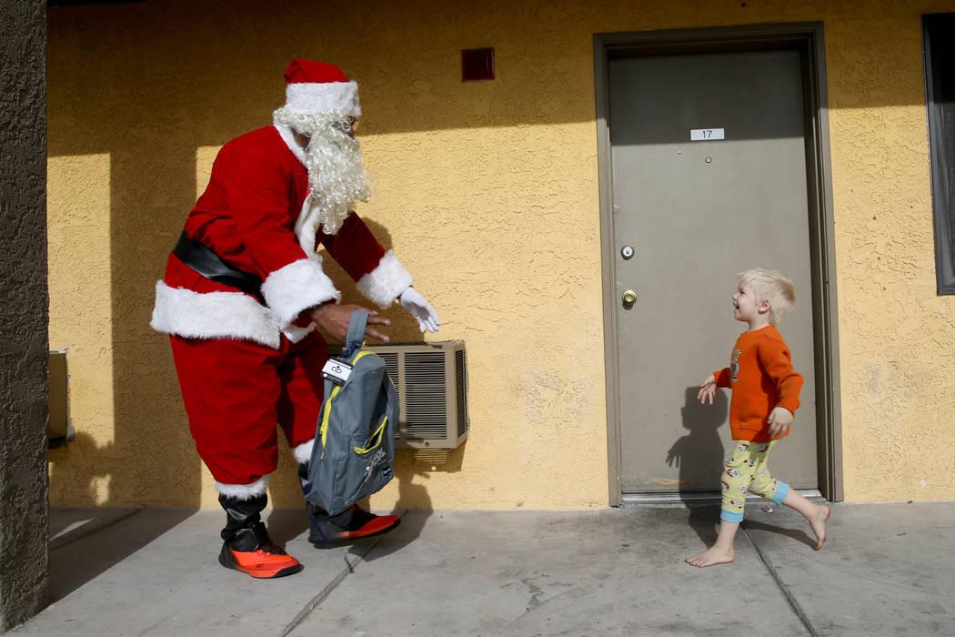 Brantley Plourde, 4, runs to Santa delivering toys at Siegel Suites Twain III in Las Vegas on Monday, Dec. 24, 2018. Kevin Cannon Las Vegas Review-Journal @kmcannonphoto