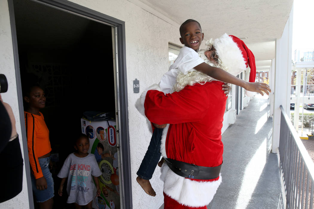 Santa delivers toys to Dereon Webster, 8, and Honesty Webster, 5, as their mom Tasheona Taylor looks on at Siegel Suites Sierra Vista in Las Vegas on Monday, Dec. 24, 2018. Kevin Cannon Las Vegas ...