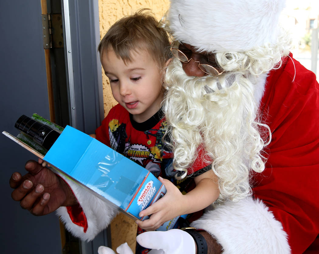 Santa delivers a toy to Leland Booth, 4, at Siegel Suites Checkmate in Las Vegas on Monday, Dec. 24, 2018. Kevin Cannon Las Vegas Review-Journal @kmcannonphoto