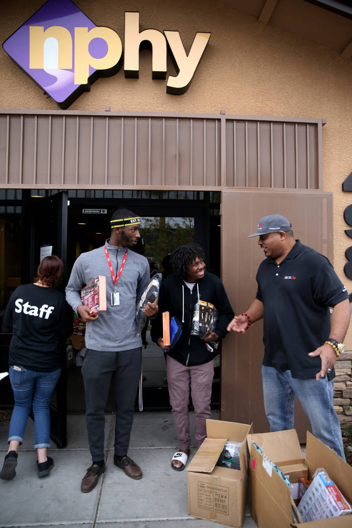 Mark Lenoir, community relations for The Siegel Group, drops off a donation Clarence, 18, left, and Tayvon, 22, at Nevada Partnership for Homeless Youth in Las Vegas Friday, Dec. 14, 2018. The don ...