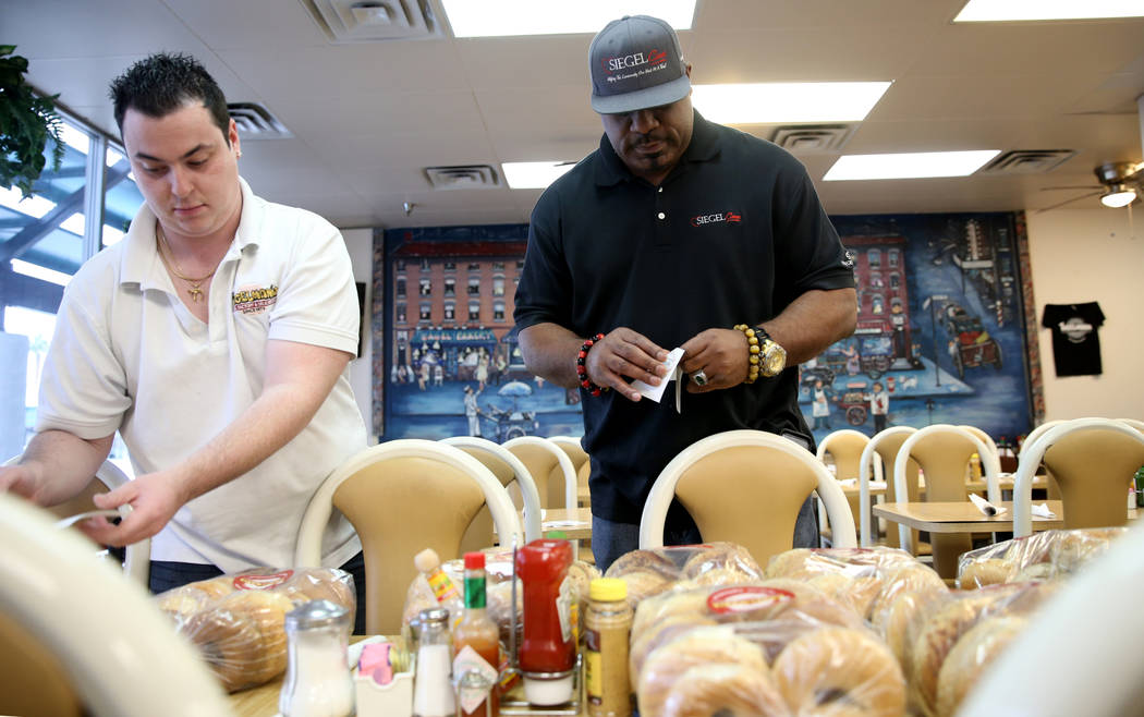 Mark Lenoir, community relations for The Siegel Group, right, picks up a donation from Bagelmania Manager Adin Rogers Las Vegas Friday, Dec. 14, 2018. Lenoir took bagels to residents at Siegel Sui ...