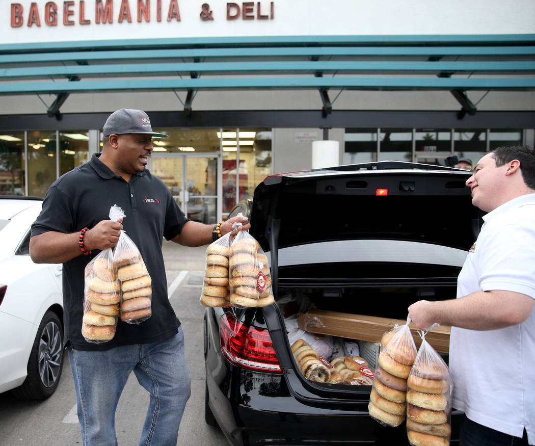 Mark Lenoir, community relations for The Siegel Group, left, picks up a donation from Bagelmania Manager Adin Rogers Las Vegas Friday, Dec. 14, 2018. Lenoir took bagles to residents at Siegel Suit ...