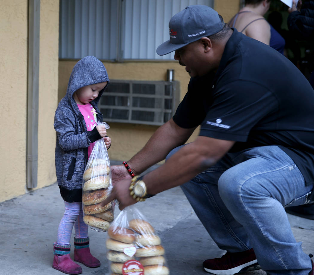 Mark Lenoir, community relations for The Siegel Group, drops off a donation of Bagelmania bagels to Katharine McCaigue, 3, at Siegel Suites Twain II in Las Vegas Friday, Dec. 14, 2018. The donatio ...