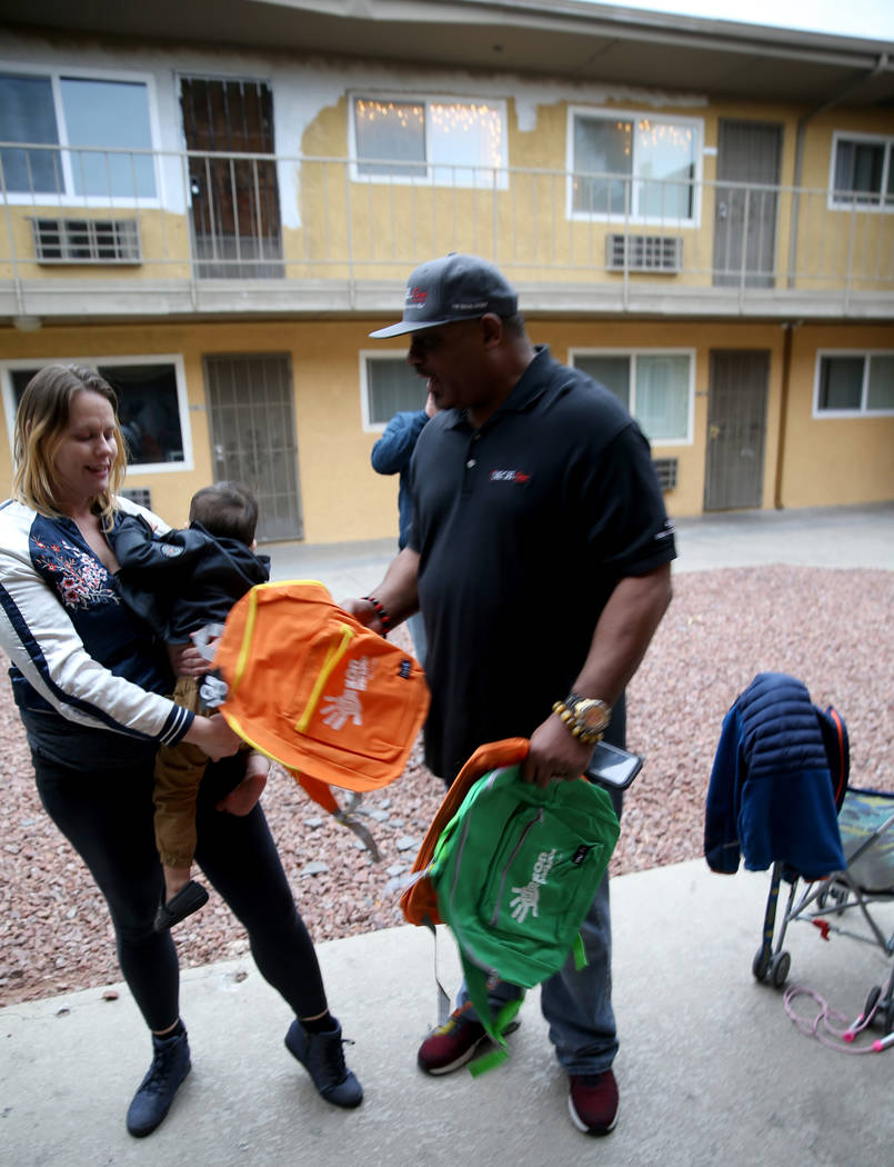 Mark Lenoir, community relations for The Siegel Group, drops off backpacks to Michelle McCaigue, 31, and her son Shawn Wayne, 2, at Siegel Suites Twain II in Las Vegas Friday, Dec. 14, 2018. The d ...