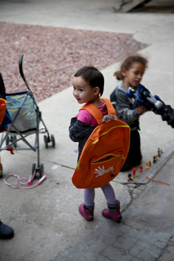 Katharine McCaigue, 3, tries out her new backpack dropped off by Mark Lenoir, community relations for The Siegel Group at Siegel Suites Twain II in Las Vegas Friday, Dec. 14, 2018. The donation is ...