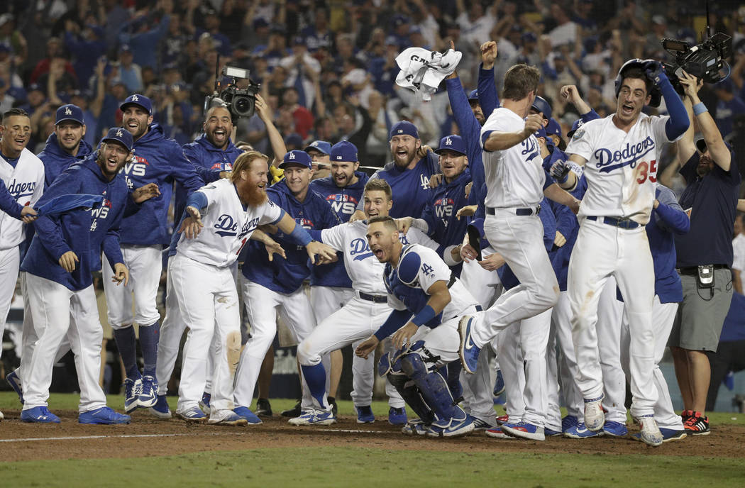 The Los Angeles Dodgers celebrates after Max Muncy's walk off during the 18th inning in Game 3 of the World Series baseball game against the Boston Red Sox on Saturday, Oct. 27, 2018, in Los Angel ...