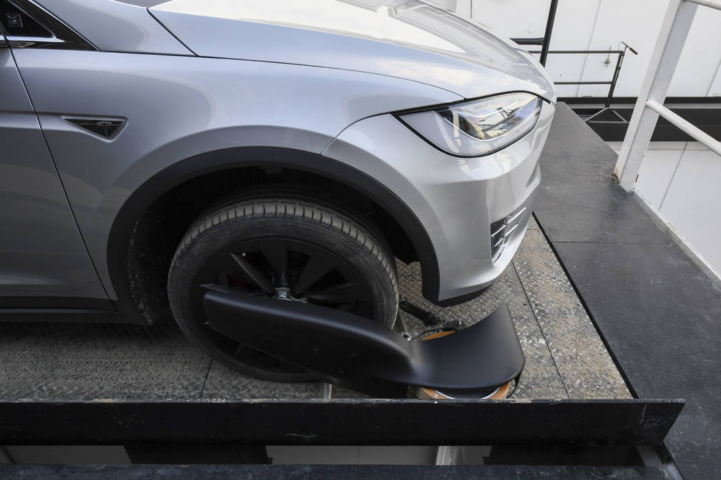 A modified Tesla Model X rests on an elevator above the pit and tunnel entrance before an unveiling event for the Boring Co. Hawthorne test tunnel in Hawthorne, Calif., Tuesday, Dec. 18, 2018. Elo ...