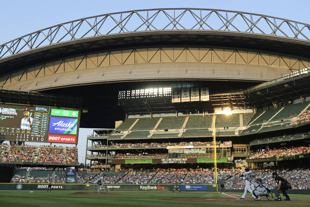 The evening sun glints off a window at Safeco Field as Seattle Mariners leadoff hitter Dee Gordon lines out against Houston Astros starting pitcher Gerrit Cole during the first inning of a basebal ...