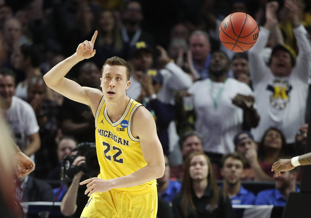Michigan guard Duncan Robinson gestures after scoring during the second half of the team's NCAA men's college basketball tournament regional final against Florida State on Saturday, March 24, 2018 ...