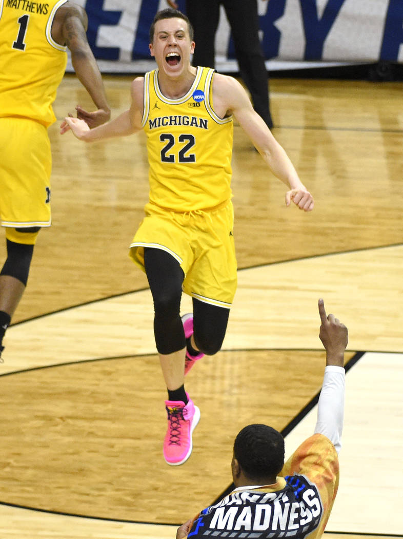 Michigan guard Charles Matthews (1) and guard Duncan Robinson (22) celebrate following an NCAA men's college basketball tournament regional final against Florida State Saturday, March 24, 2018, in ...