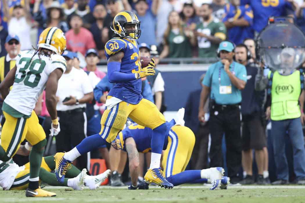 Los Angeles Rams running back Todd Gurley (30), right, slows down and and allows Green Bay Packers cornerback Tramon Williams (38) to catch up rather than making the easy score to allow the time t ...