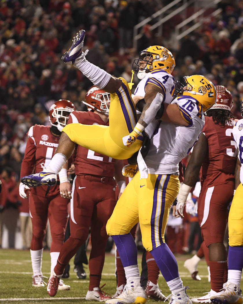 LSU running back Nick Brossette celebrates with teammate Austin Deculus after scoring a touchdown in the first half of an NCAA college football game against Arkansas, Saturday, Nov. 10, 2018, in F ...