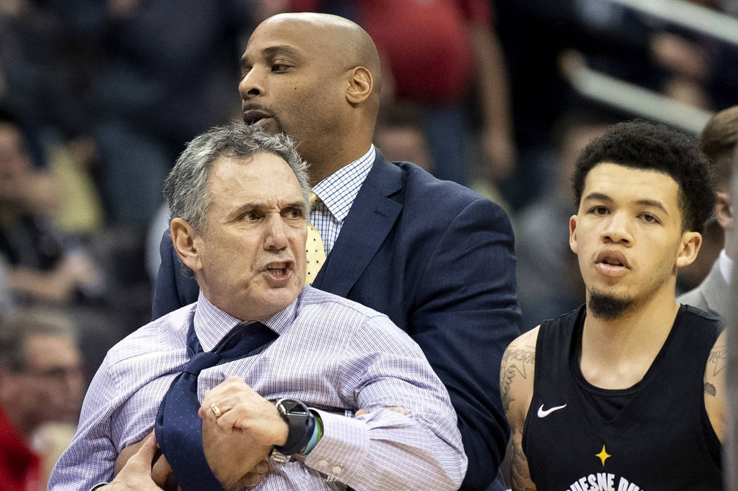 Duquesne head coach Keith Dambrot is held back by assistant coach Charles Thomas and Tavian Dunn-Martin after Dambrot was ejected from the NCAA college basketball game late in the fourth quarter a ...