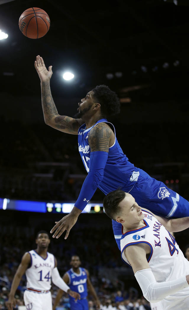 Seton Hall guard Myles Powell shoots over Kansas forward Mitch Lightfoot (44) during the first half of an NCAA men's college basketball tournament second-round game Saturday, March 17, 2018, in Wi ...