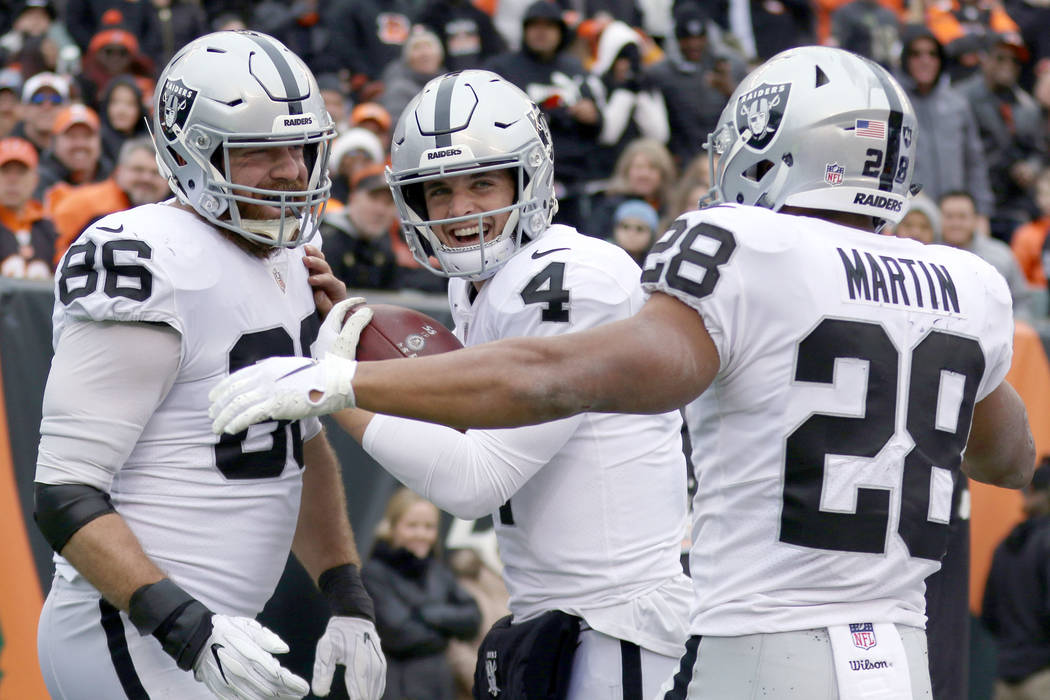 Oakland Raiders quarterback Derek Carr (4) celebrates his touchdown pass to tight end Lee Smith (86) with running back Doug Martin (28) during the first half of an NFL game against the Cincinnati ...
