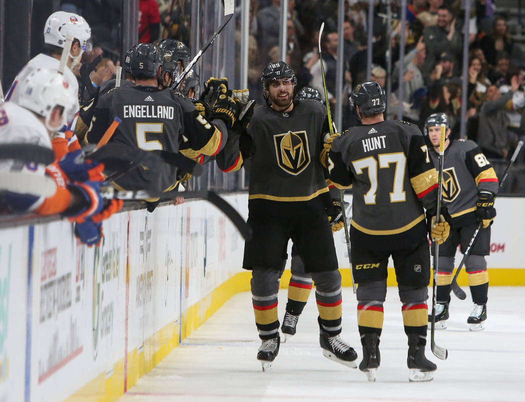 Vegas Golden Knights right wing Alex Tuch (89) high fives the bench after scoring a goal against the New York Islanders before it was taken away for being offsides during the second period of an N ...