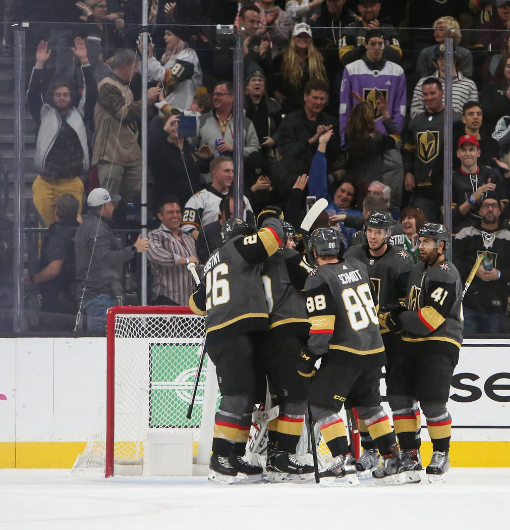 The Vegas Golden Knights celebrate after Vegas Golden Knights defenseman Nate Schmidt (88) scores an empty net goal against the New York Islanders during the third period of an NHL hockey game at ...