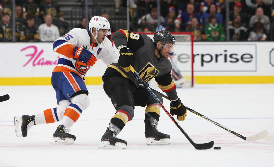 Vegas Golden Knights left wing William Carrier (28) protects the puck while under pressure from New York Islanders right wing Cal Clutterbuck (15) during the second period of an NHL hockey game at ...