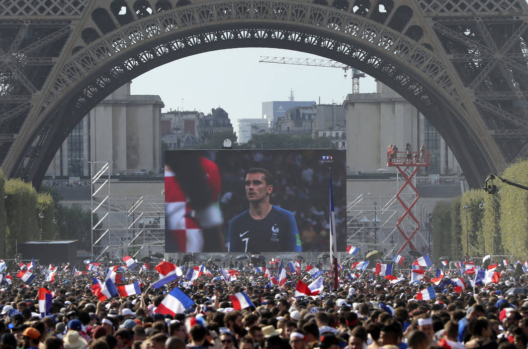 In this Sunday, July 15, 2018 file photo, people watch a giant screen during the World Cup final between France and Croatia, on the Champ de Mars next to the Eiffel Tower in Paris. (AP Photo/Bob E ...