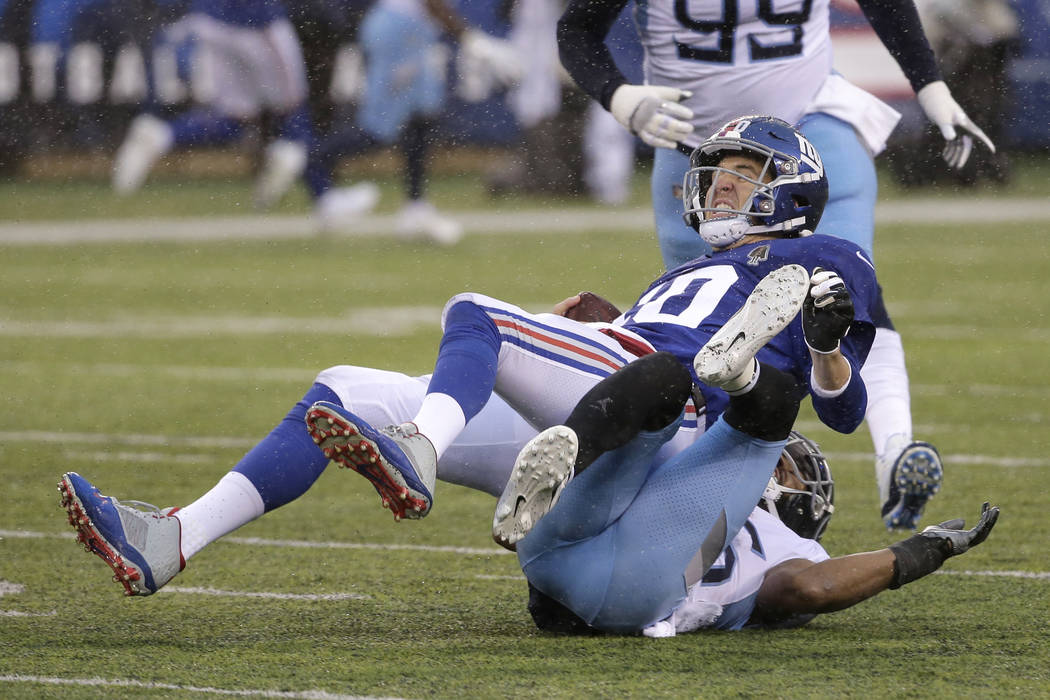 New York Giants quarterback Eli Manning, top, is sacked by Tennessee Titans cornerback Logan Ryan during the first half of an NFL football game, Sunday, Dec. 16, 2018, in East Rutherford, N.J. (AP ...