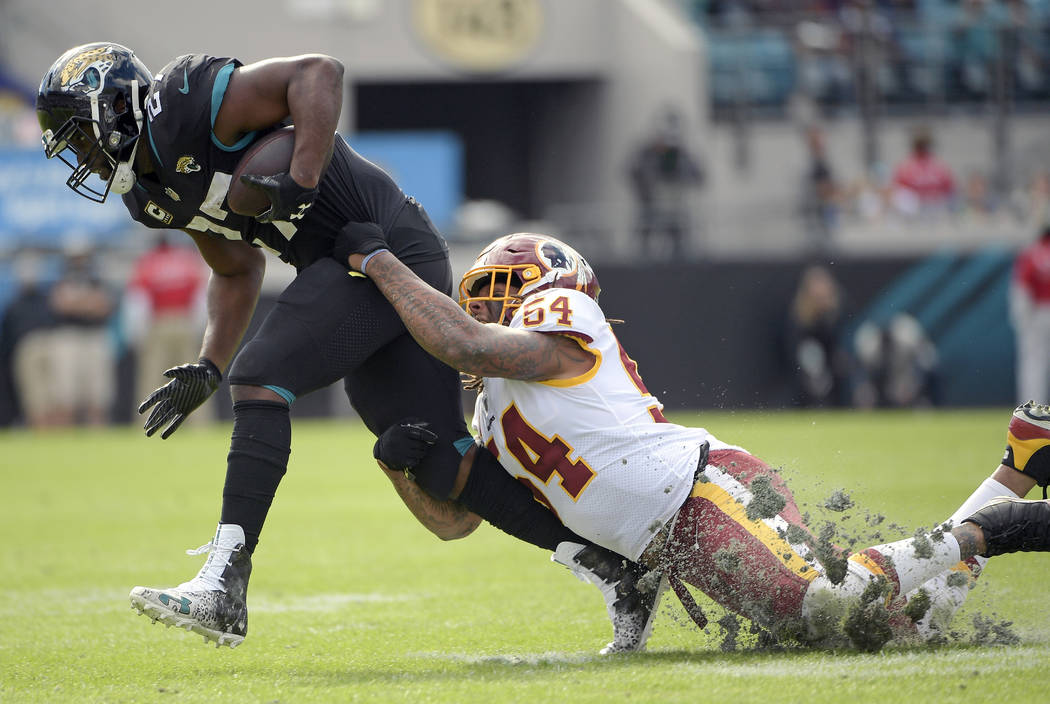 Jacksonville Jaguars running back Leonard Fournette, left, is stopped by Washington Redskins inside linebacker Mason Foster (54) after a pass reception during the first half of an NFL football gam ...