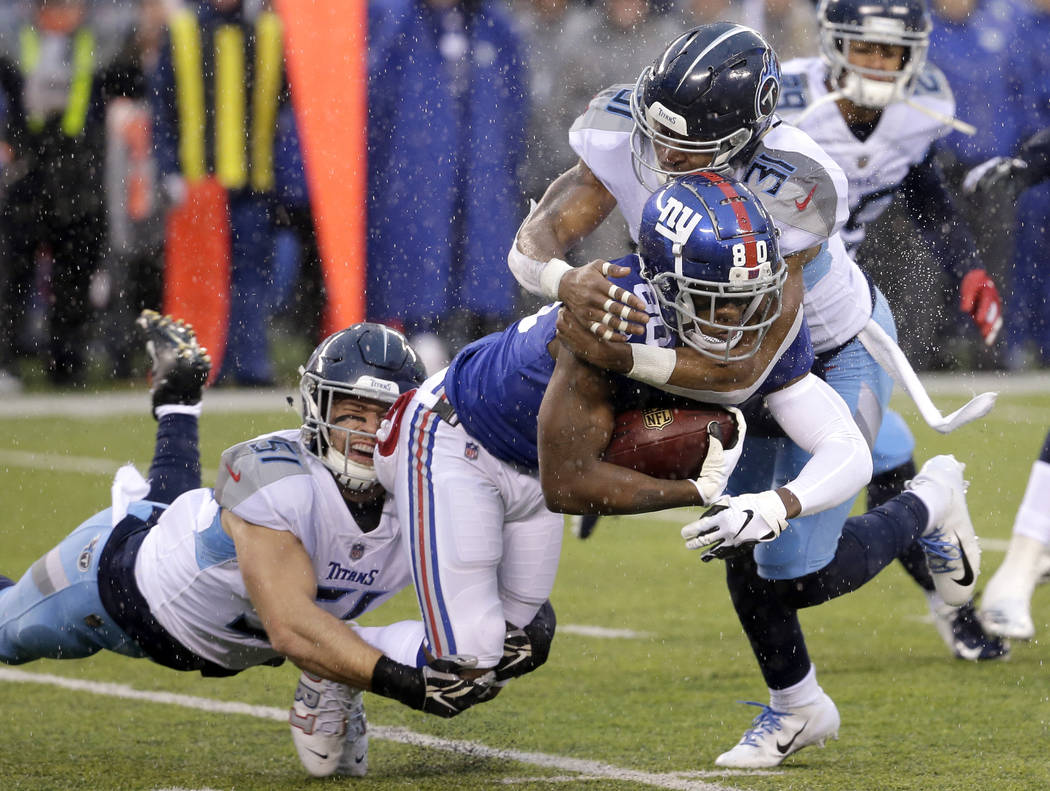 New York Giants wide receiver Jawill Davis, center, is tackled by Tennessee Titans inside linebacker Will Compton, left, and free safety Kevin Byard during the first half of an NFL football game S ...