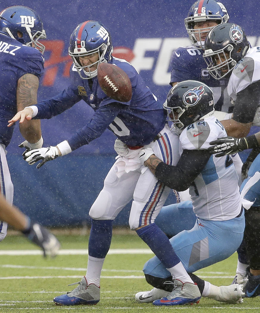 New York Giants quarterback Eli Manning, left, fumbles the ball as Tennessee Titans outside linebacker Kamalei Correa applies pressure during the second half of an NFL football game, Sunday, Dec. ...