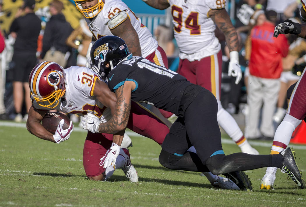 Washington Redskins cornerback Fabian Moreau (31) is tackled by Jacksonville Jaguars wide receiver Donte Moncrief (10) after incepting a pass during the final minutes of an NFL football game, Sund ...