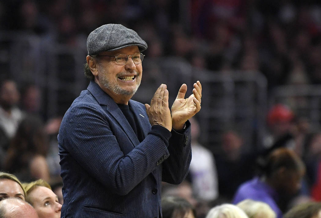 In this March 9, 2018, file photo, actor Billy Crystal applauds during the second half of an NBA basketball game between the Los Angeles Clippers and the Cleveland Cavaliers in Los Angeles. (AP Ph ...