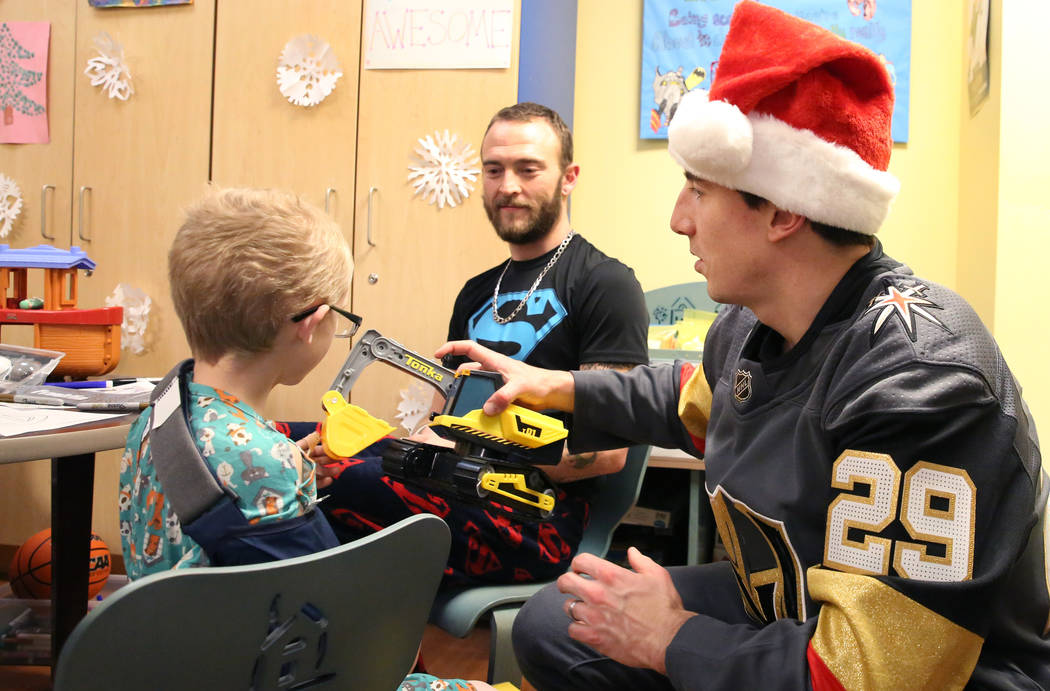 Brayden Pena, 6, watches as Golden Knights player Marc-Andre Fleury delivers his toy as his father Adam, center, looks on at Summerlin Hospital Medical Center on Friday, Dec. 21, 2018. Players vis ...