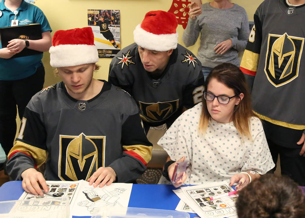 Megan Kral, center, plays Bingo with Golden Knights player William Karlsson, left, as Marc-Andre Fleury, center, looks on at Summerlin Hospital Medical Center on Friday, Dec. 21, 2018. Players vis ...
