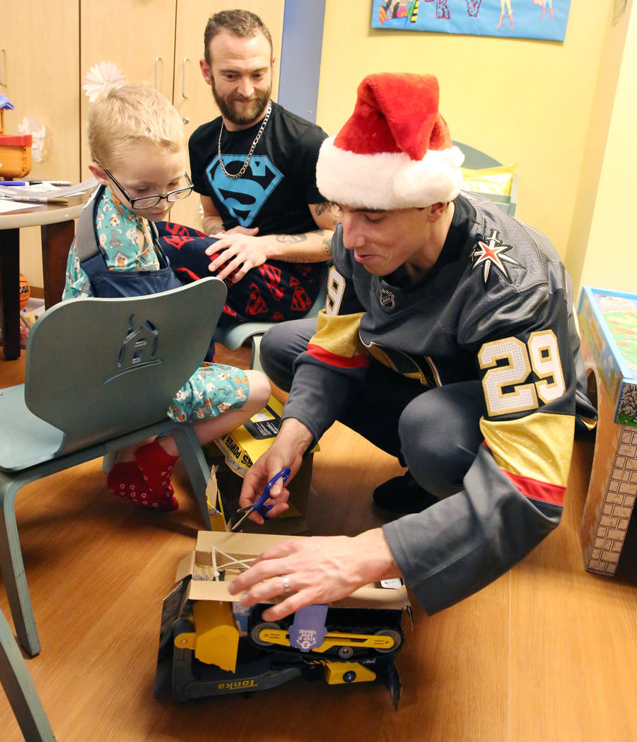 Brayden Pena, 6, watches as Golden Knights player Marc-Andre Fleury opens his toy as his father Adam looks on at Summerlin Hospital Medical Center on Friday, Dec. 21, 2018. Players visited the hos ...