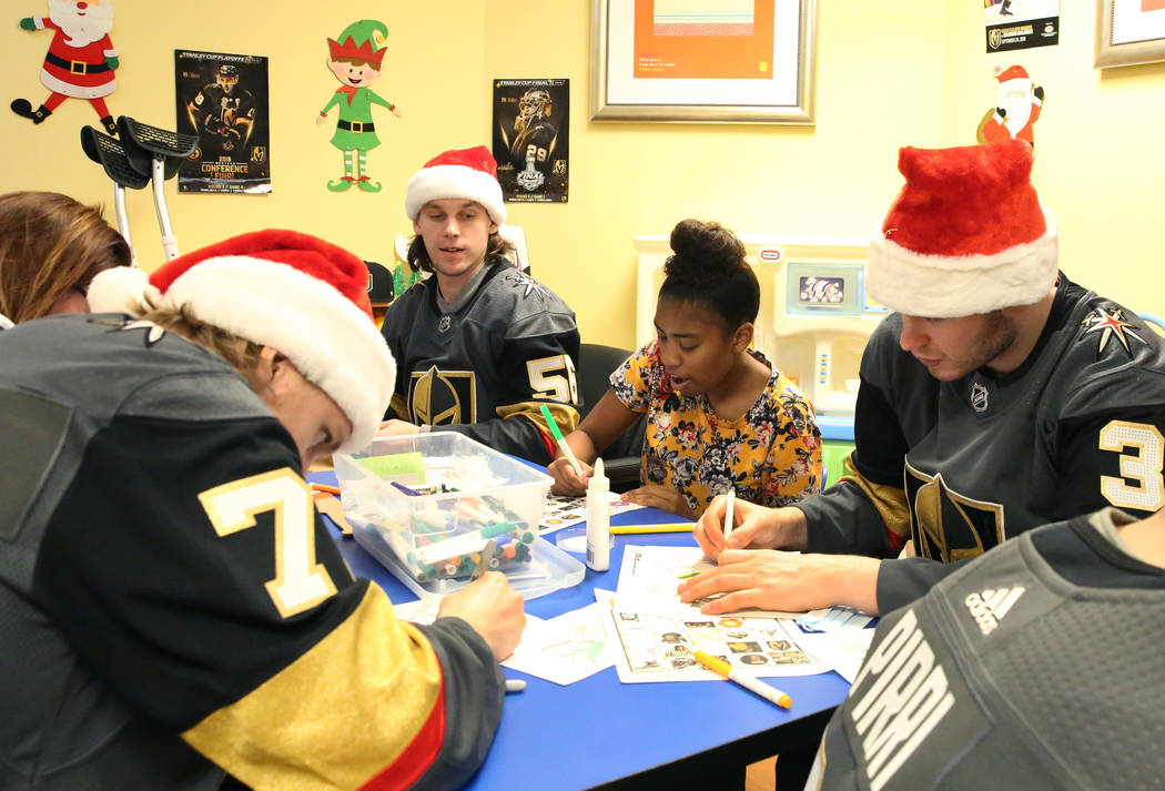Dijeauna Briggs, center, colors with Golden Knights players William Karlsson, left, Erik Haula, second left, and Brayden McNabb, right, at Summerlin Hospital Medical Center on Friday, Dec. 21, 201 ...