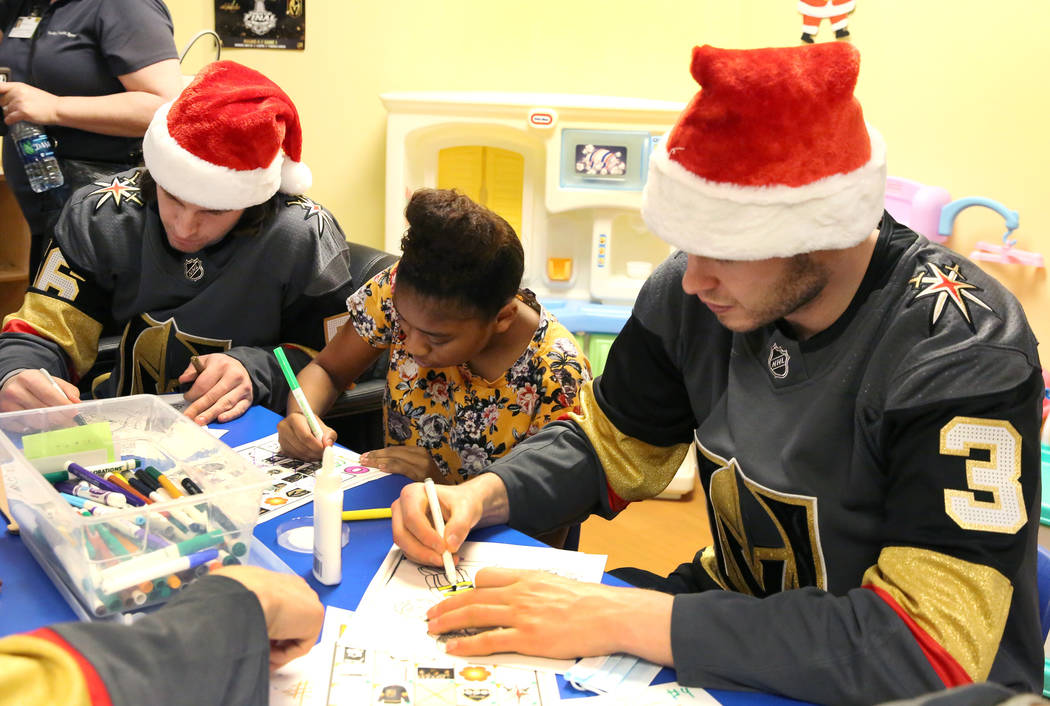 Dijeauna Briggs, center, colors with Golden Knights players Erik Haula, left, and Brayden McNabb at Summerlin Hospital Medical Center on Friday, Dec. 21, 2018. Players visited the hospital to deli ...