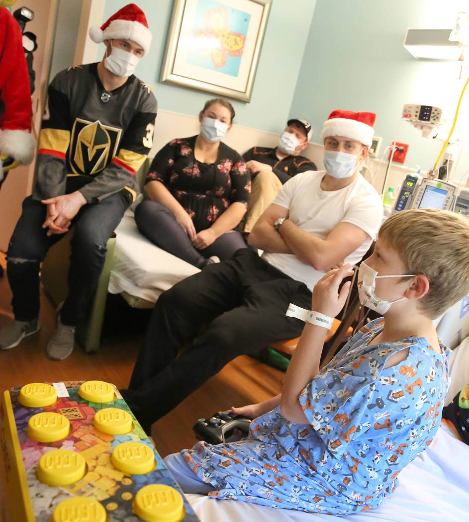 Jacob Bailey, 7, right, chats with Golden Knights players Nate Schmidt, second right, and Brayden McNabb, left, after receiving a Lego at Summerlin Hospital Medical Center as his mother Rachel, se ...