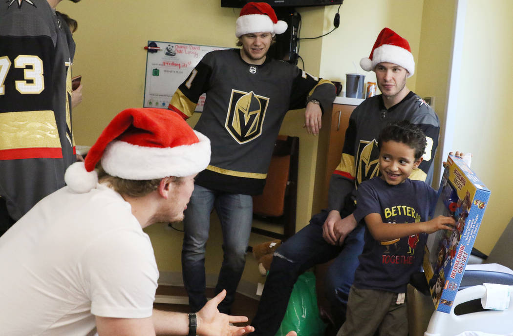 Israel Ugarte, 6, right, chats with Golden Knights players Nate Schmidt, left, William Karlsson, center, and Brayden McNabb, right, after receiving a toy at Summerlin Hospital Medical Center on Fr ...